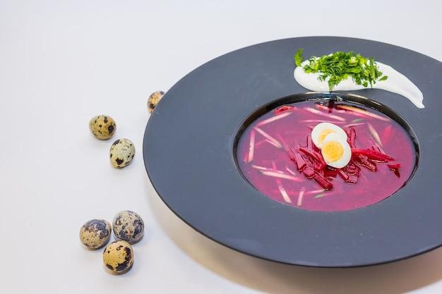 Sopa tradicional con remolacha y verduras en plato negro.