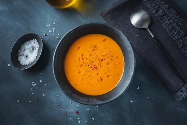 Sopa vegana de puré de otoño con calabaza y jengibre en un tazón servido sobre fondo oscuro. de cerca