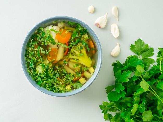 Sopa vegetariana dietética vegetal de la primavera sana, fondo concreto gris