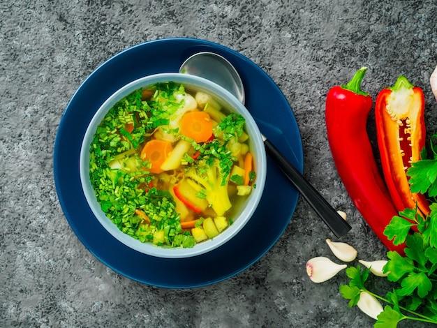 Sopa vegetariana dietética vegetal sana de la primavera, fondo concreto oscuro gris