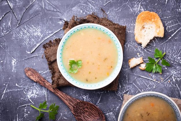 Sopa vegetariana sana de los guisantes en fondo concreto