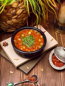 Sopa de verduras de calabacín de tomate con hierbas en un tazón negro sobre los libros