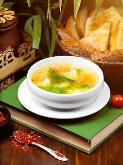 Sopa de verduras casera de pollo, vista desde arriba sobre un libro sobre la mesa