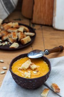 Sopa de verduras puré de calabaza, zanahorias y apio, servido con picatostes y semillas de calabaza. estilo rústico