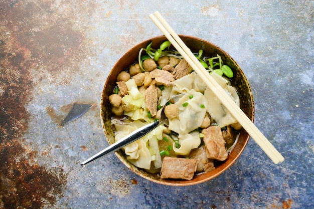 Sopa de wonton con albóndigas de carne, cebolleta servida en un tazón grande y marrón