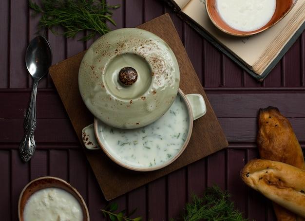 Sopa de yogur con verduras dentro de una sartén sobre una plancha de madera.