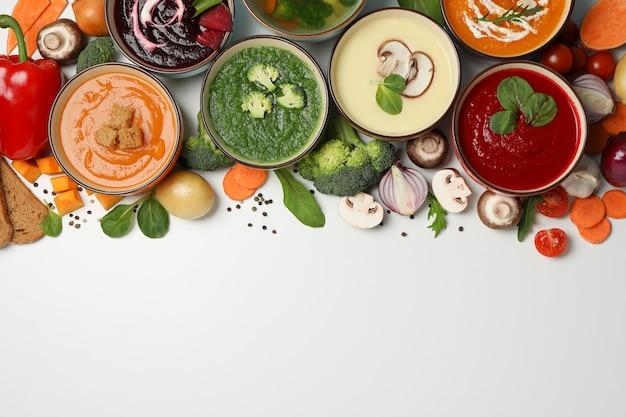 Sopas de verduras e ingredientes en blanco, espacio para texto