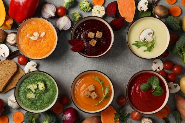 Sopas de verduras e ingredientes en gris, vista superior