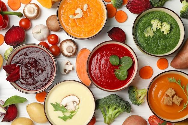 Sopas de verduras e ingredientes en madera blanca, vista superior