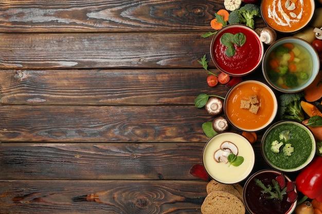 Sopas de verduras e ingredientes en madera, espacio para texto
