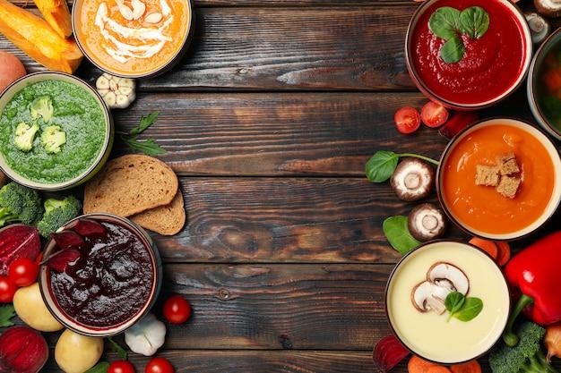 Sopas de verduras e ingredientes en madera, vista superior