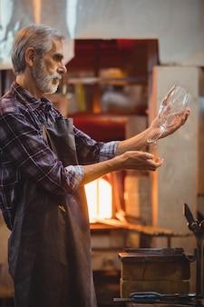 Soplador de vidrio examinando la cristalería