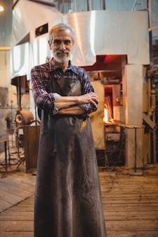 Soplador de vidrio de pie con los brazos cruzados en la fábrica de vidrio soplado