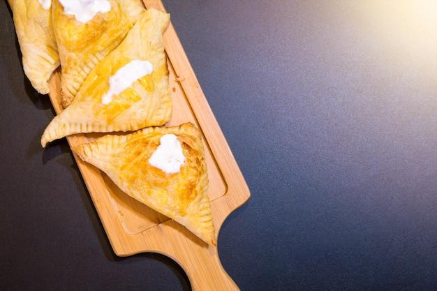 Soplos con requesón y crema agria en una bandeja de madera.