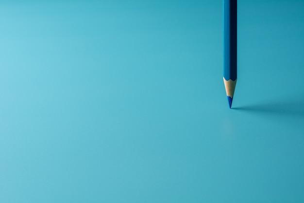 Soporte azul del lápiz del creyón en fondo del papel azul. - concepto de negocio