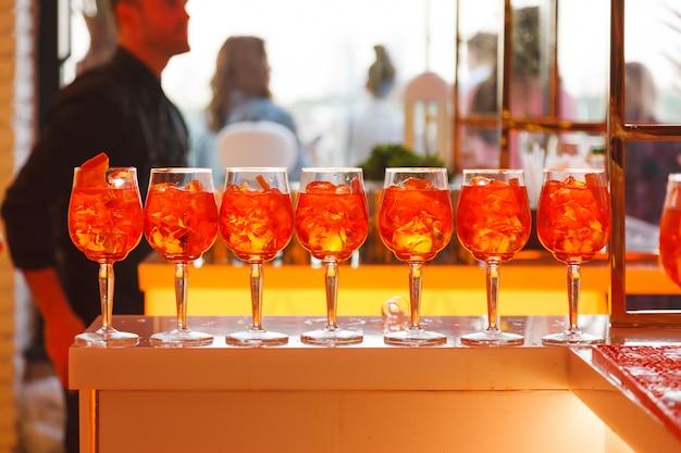 En el soporte del bar hay vasos con bebida fría de naranja.