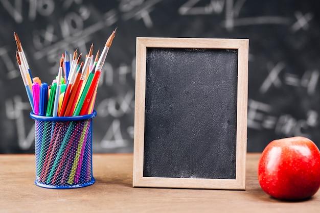 Soporte para bolígrafo y pizarra en blanco con manzana colocada en el escritorio