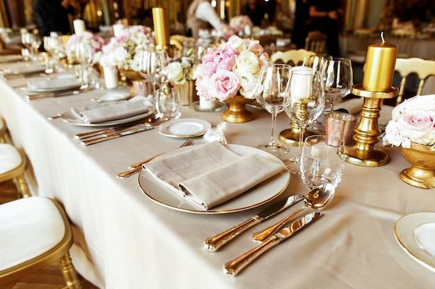 Soporte brillante de cristalería y cubertería sobre la mesa decorada
