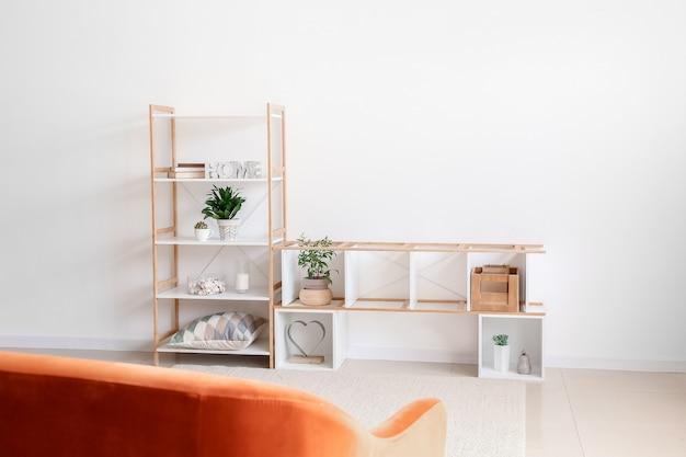 Soporte y estante con estilo con decoración cerca de la pared clara en la habitación