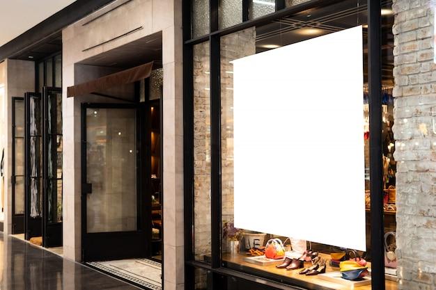 Soporte de exhibición de cartel de promoción en blanco en la tienda de ropa o tienda.