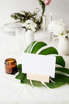 Soporte para folletos con papel blanco, tarjeta de carpa de madera en hoja de monstera en mesa de restaurante