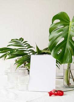 Soporte para folletos con papel blanco, tarjeta de carpa de madera en la mesa del restaurante con ramo tropical