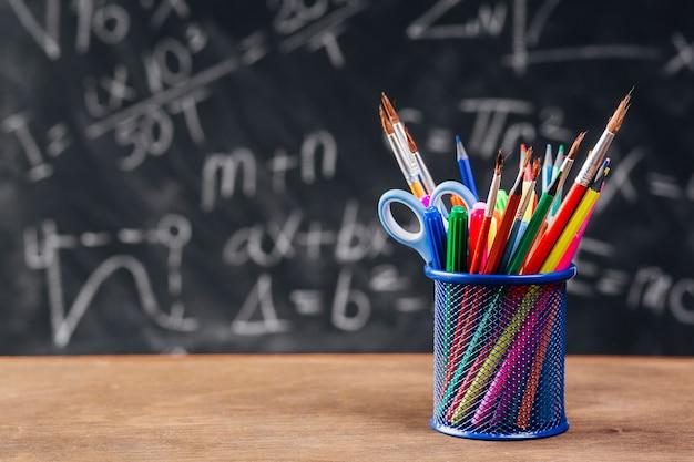 Soporte para lápiz azul con herramientas de dibujo colocadas en el escritorio