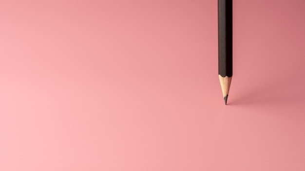 Soporte de lápiz sobre fondo de papel rosa