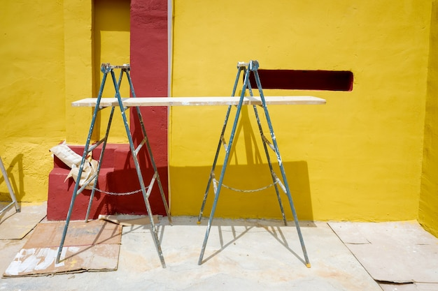 Soportes y andamios con tablas de madera que utiliza un pintor para pintar una pared.