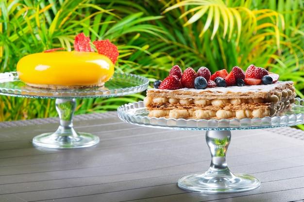 Soportes de pastel con postres creativos sobre fondo tropical.