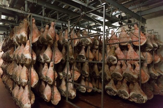 Sorage de jamón serrano en la fábrica de jamón de bolonia, italia