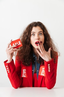 Sorprende joven mujer adicta a las compras con cartel de venta