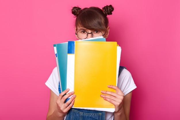 Sorprendida emotiva mujer europea se esconde detrás de coloridas carpetas de papel, usa gafas negras redondas, camiseta blanca, overol de mezclilla, se levanta contra rosa