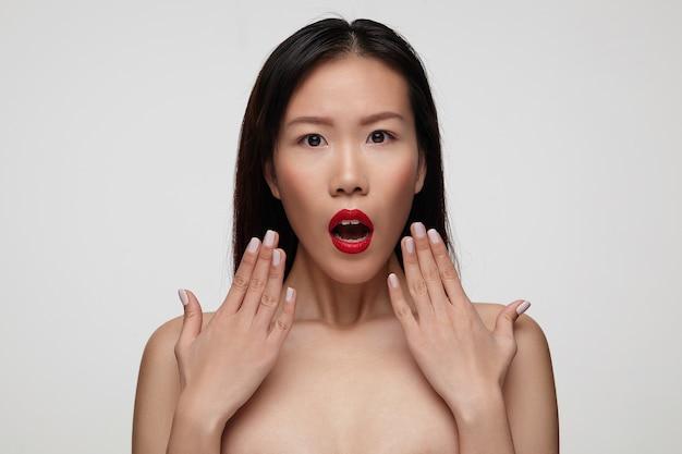 Sorprendida joven mujer de pelo bastante oscuro con labios rojos manteniendo sus palmas cerca de su cara y con la boca abierta, de pie contra la pared blanca