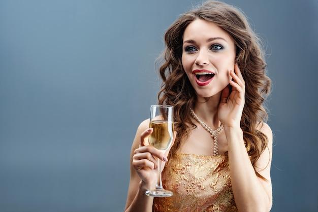 Sorprendida mujer en vestido dorado y collar de perlas con copa de champán levantada y tocarse cara a cara