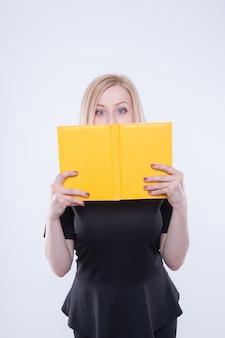 Sorprendida y sorprendida mujer de negocios en vestido negro se asoma desde un bloc de notas