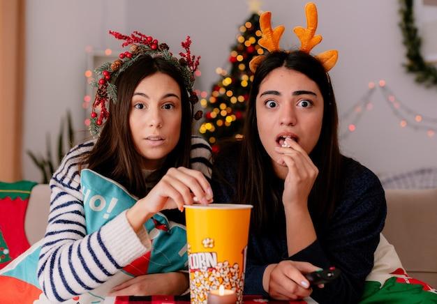 Sorprendidas chicas jóvenes con corona de acebo y diadema de renos comen palomitas de maíz viendo la televisión sentadas en sillones y disfrutando de la navidad en casa