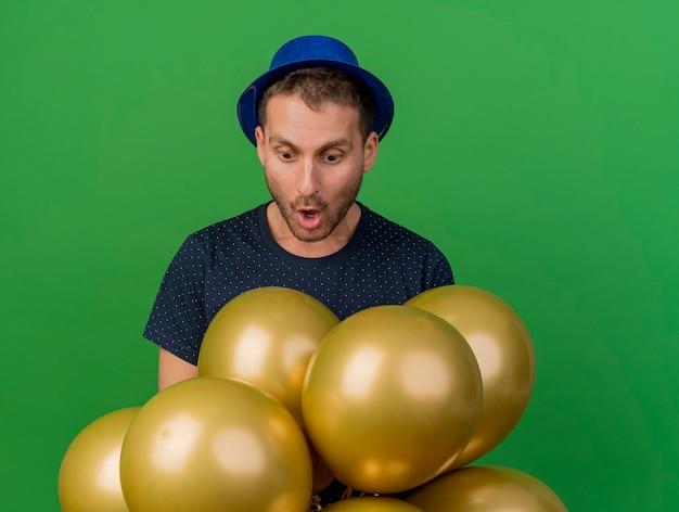 Sorprendido apuesto hombre caucásico vestido con gorro de fiesta azul mira globos de helio aislados sobre fondo verde con espacio de copia