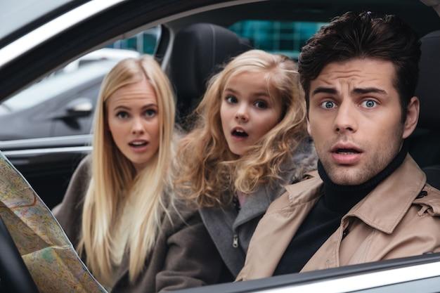Sorprendido asustado joven familia sosteniendo mapa.