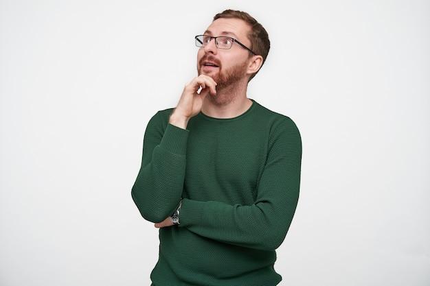 Sorprendido atractivo joven morena barbudo con gafas sosteniendo su barbilla y mirando asombrado hacia arriba, vestido con jersey verde