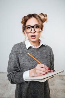Sorprendido confundido joven de gafas de pie y escribiendo