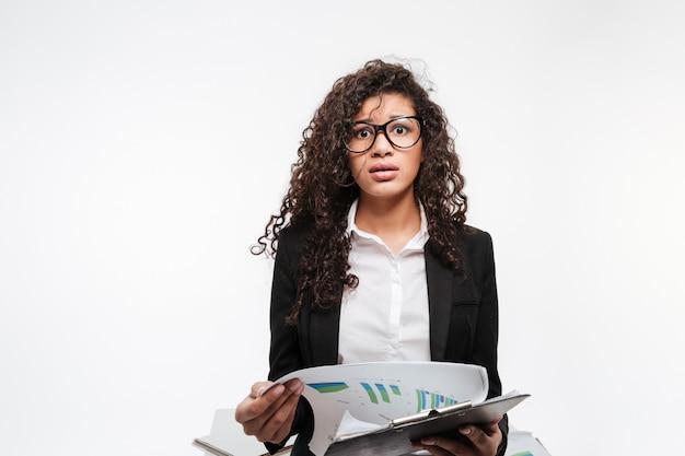 Sorprendido dama de negocios africanos con gafas leyendo gaceta