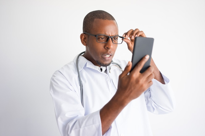 Sorprendido doctor hombre negro leyendo noticias sobre el teléfono inteligente.