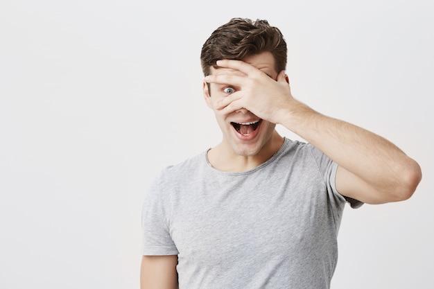Sorprendido emocional joven europeo que sorprendió la mirada fascinada, abriendo la boca ampliamente y ocultando la cara detrás de la palma, de pie aislado contra el fondo de la pared del estudio en blanco