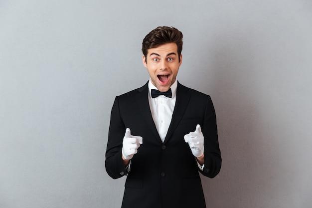 Sorprendido feliz joven camarero apuntando a usted.