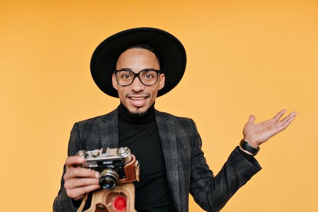Sorprendido fotógrafo masculino con sombrero negro. foto interior de joven africano con cámara aislada en pared amarilla.