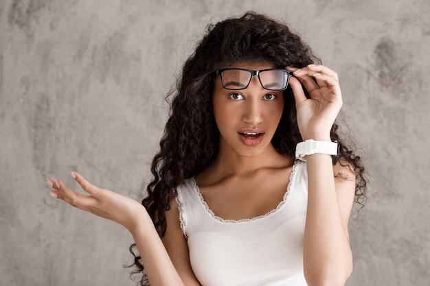 Sorprendido gafas de despegue de mujer de pelo rizado