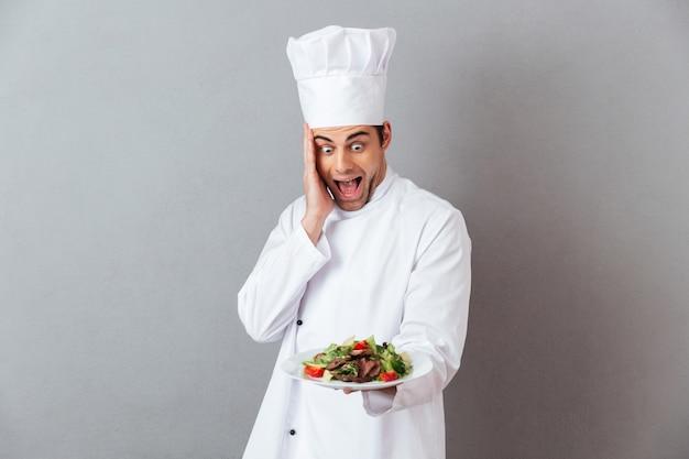 Sorprendido gritando joven cocinero en uniforme con ensalada.