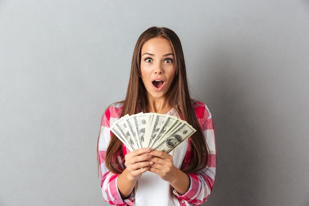 Sorprendido hermosa joven morena en camisa a cuadros con dinero