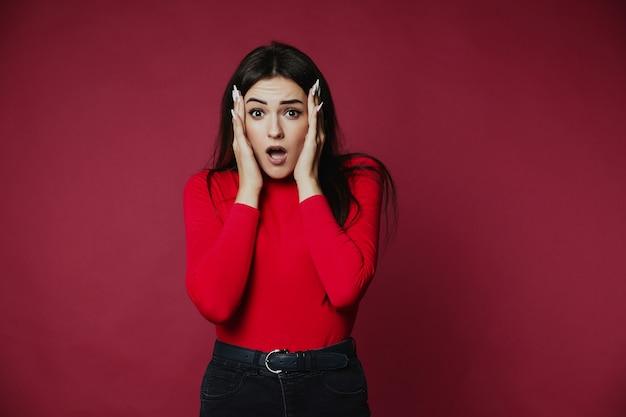 Sorprendido hermosa morena caucásica chica vestida con un jersey rojo está sosteniendo la cabeza en las manos